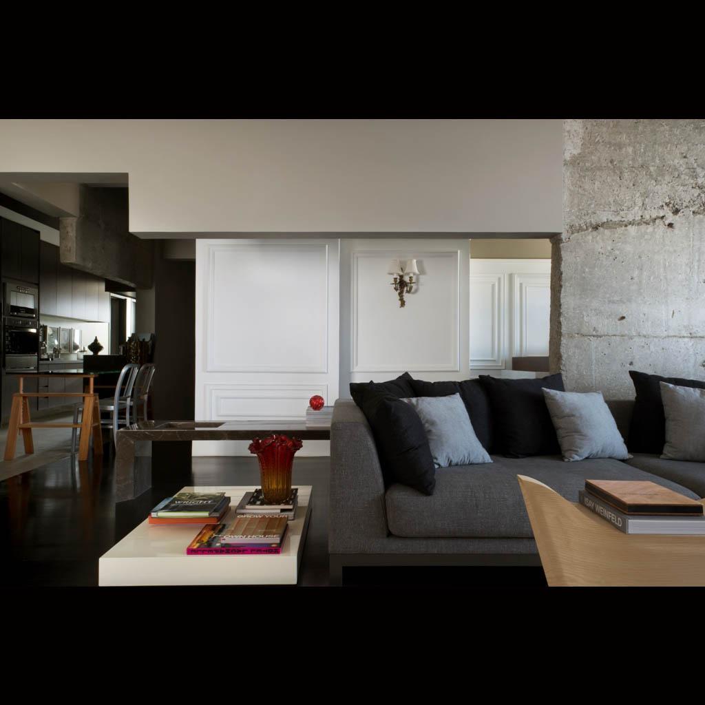 As paredes foram retiradas para criar um grande living, que integra sala, escritório e cozinha. A coluna de concreto aparente e as paredes com recortes em zigue-zague causam um efeito interessante e contrastam com a parede branca com molduras e arandela