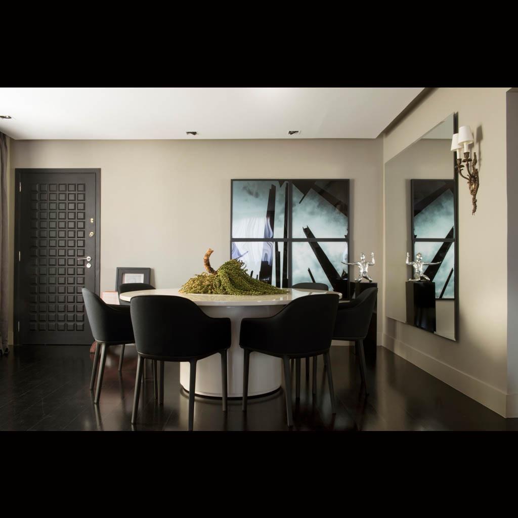 A mesa de jantar redonda fica na entrada do apartamento. É de laca brilhante e se destaca sobre o piso preto, cadeiras de design alemão e espelhos completam a composição