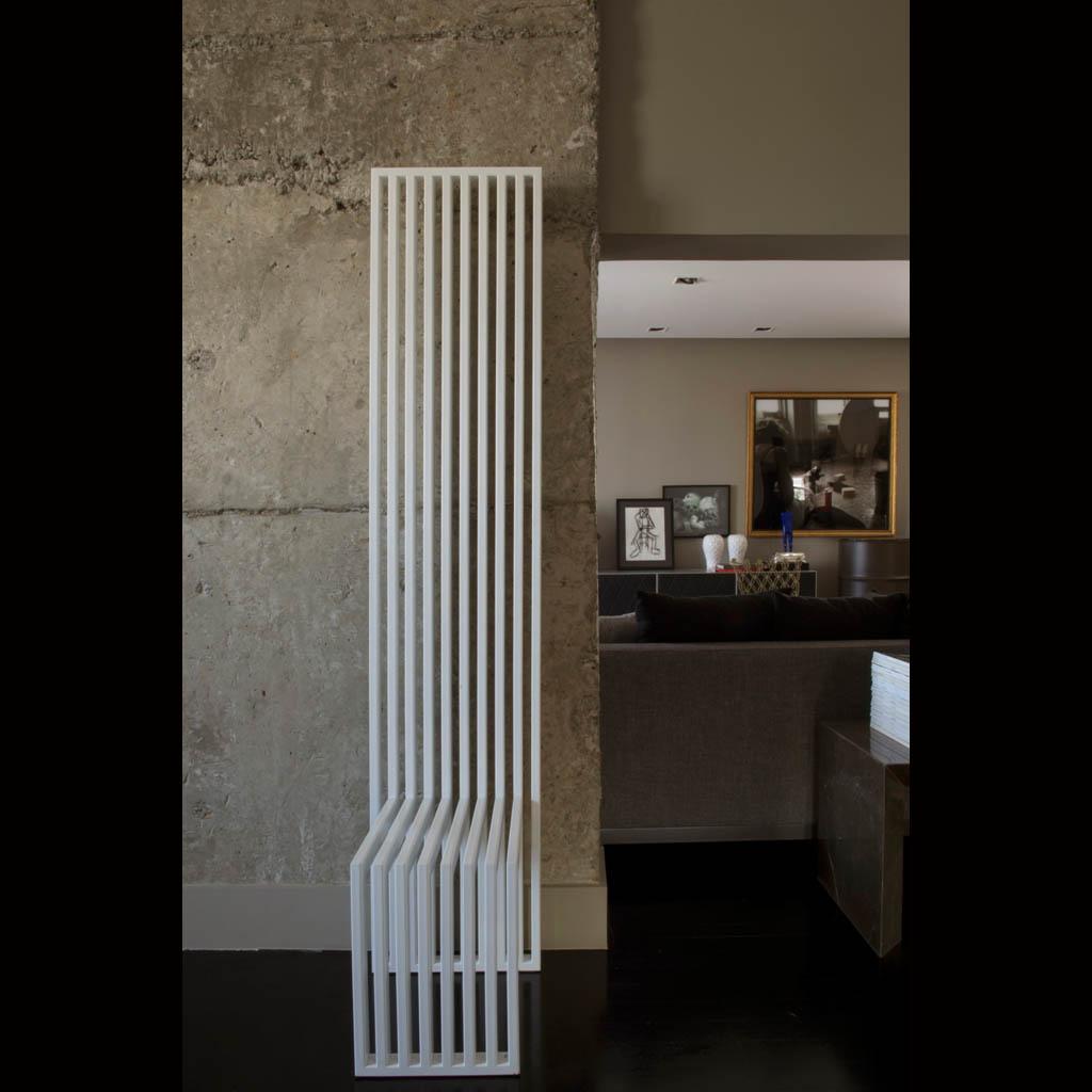 A cadeira Long Nest da Érea em conjunto com a parede de cimento bruto dão ar industrial ao escritório