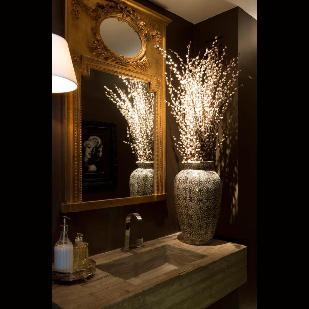 No lavabo, a bancada contemporânea em concreto moldada no próprio local contrasta com o espelho clássico dourado