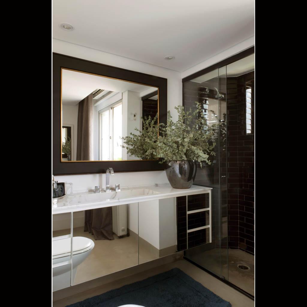 A suíte tem piso de cimento queimado, bancada de mármore e paredes com revestimento preto brilhante na área de banho