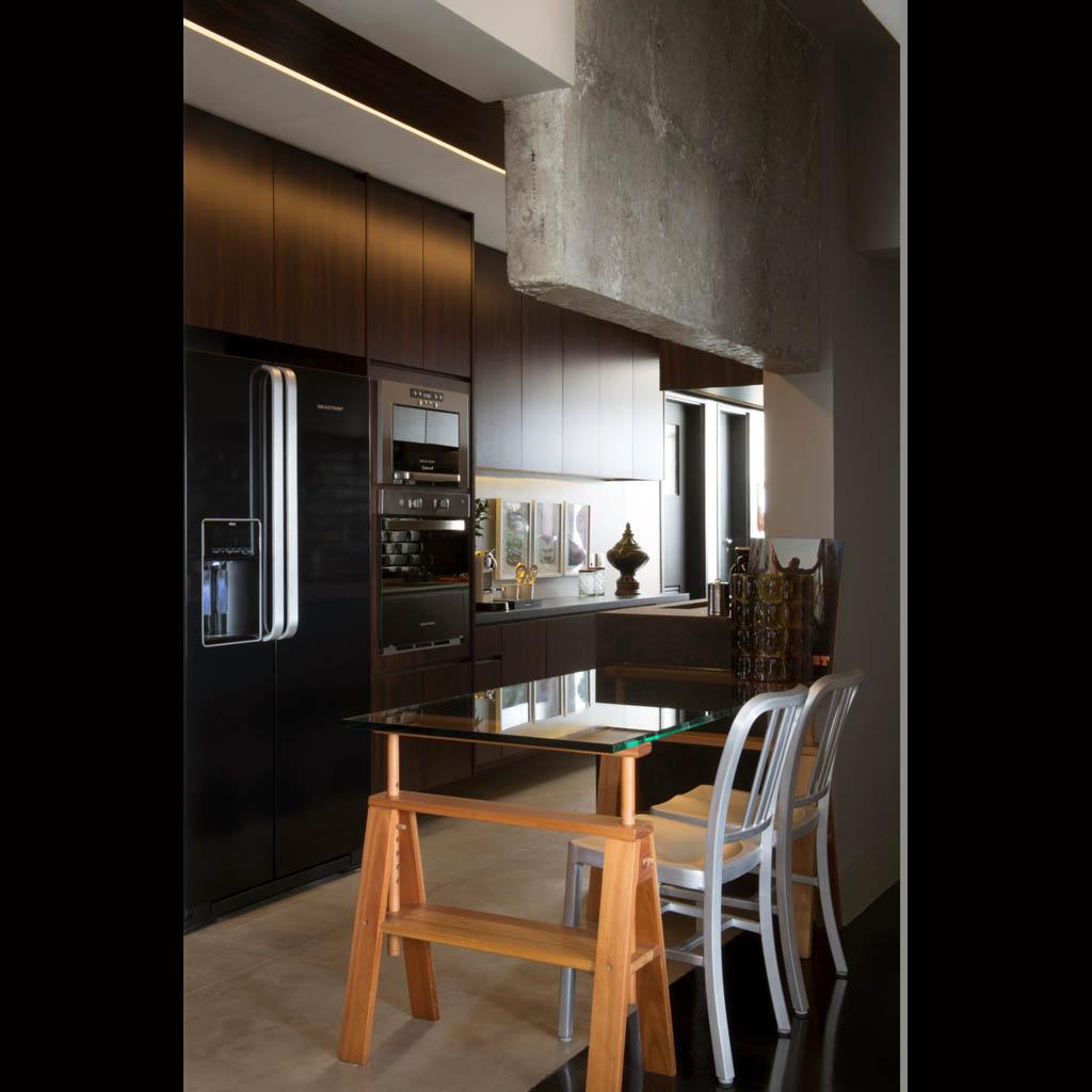 A separação da cozinha fica evidente pelo detalhe da coluna aparente e piso em cimento queimado